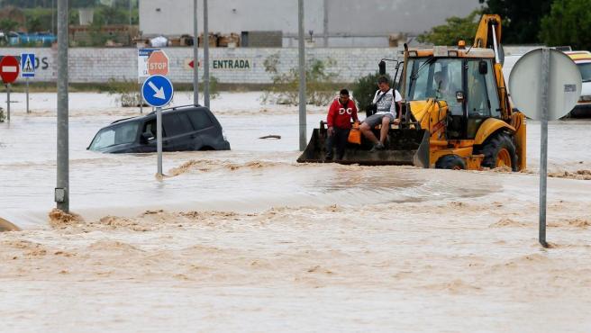 Dos ocupantes de un vehículo son rescatados por una pala mecánica en Orihuela.