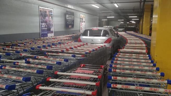 Imagen del coche totalmente rodeado por carritos de la compra.