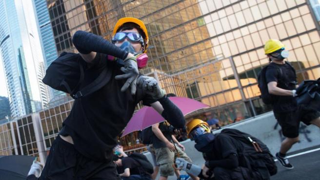 Un manifestante lanza piedras durante las protestas en Hong Kong.