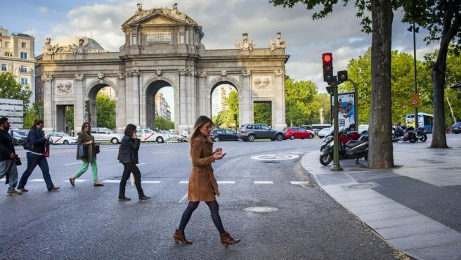 Varias personas cruzan un paso de peatones junto a la Puerta de Alcalá de Madrid.