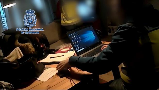 Imagen de archivo de un agente de la Policía Nacional con material informático.
