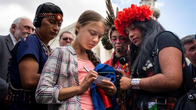 La activista climática sueca y fundadora del movimiento Fridays for Future Greta Thunberg firma una tarjeta a la activista panameña Militza Flaco frente al Tribunal Supremo de EE UU, en Washington.