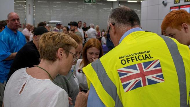 Un empleado del gobierno británico atiende a una pasajera en el aeropuerto de Palma de Mallorca.
