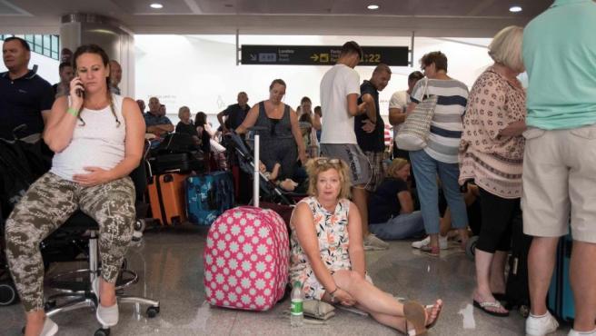 Varios pasajeros esperan pacientemente en la terminal del aeropuerto de Menorca, tras las cancelaciones de vuelos por la quiebra del touroperador Thomas Cook.