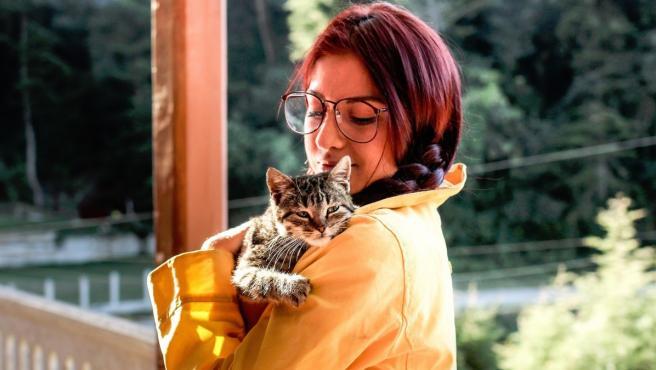 Una mujer abrazada a su gato.