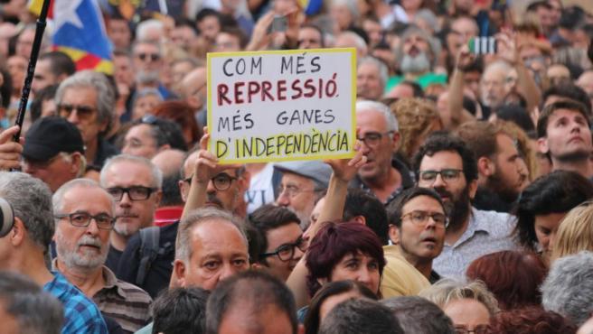 Un manifestante muestra un cartel contra las 9 detenciones de miembros de los CDR con la frase en catalán 'Cuanta más represión más ganas de independencia'.