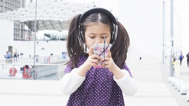 Una niña pequeña con un móvil.