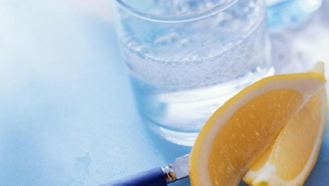 Imagen de archivo de un vaso de agua y unos trozos de limón.