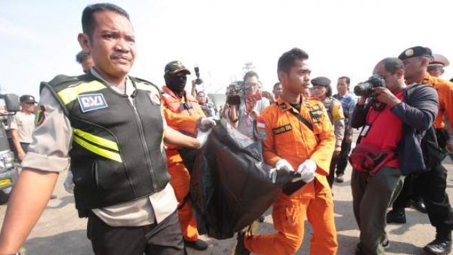 Equipos de rescate con uno de los cadáveres del avión estrellado en el mar de Java (Indonesia).
