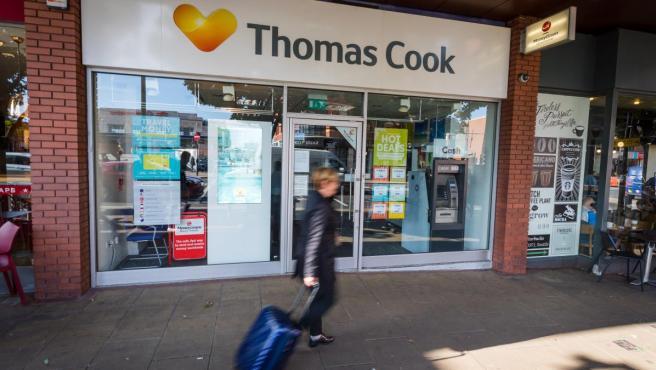 Una mujer con una maleta pasa junto a una agencia Thomas Cook cerrada, en Londres (Reino Unido).