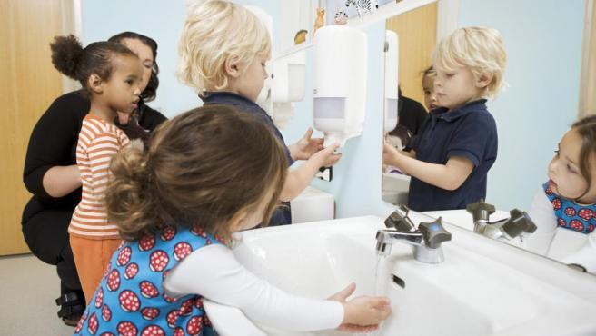 Imagen de varios niños lavándose las manos en el colegio.