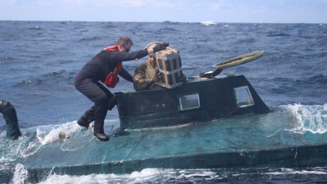 Miembros de los guardacostas estadounidenses sacan del submarino uno de los fardos de cocaína.