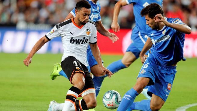 Coquelín y Cabrera pugnan por un balón durante el Valencia - Getafe.