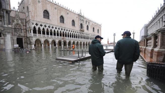 Dos personas caminan por la inundada plaza de San Marcos en Venecia.