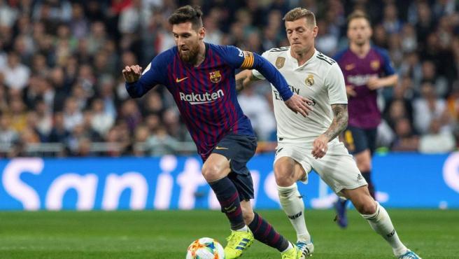 Toni Kroos persigue a Leo Messi durante un partido entre Barcelona y Real Madrid.