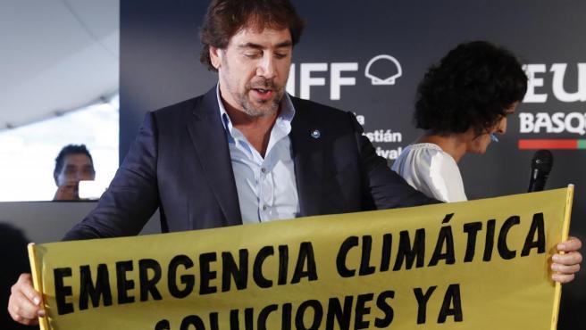 """En la foto, el actor Javier Bardem sujeta una pancarta de Greenpeace que dice """"Emergencia climática. Soluciones ya""""."""
