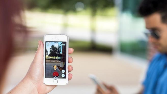 Dos personas jugando a 'Pokémon Go' en sus móviles.