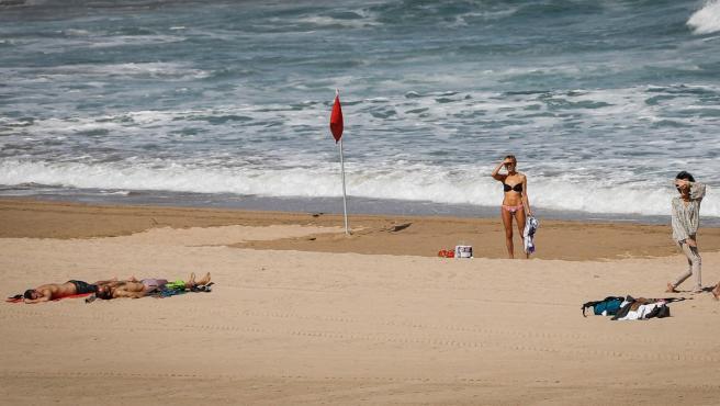 Varias personas disfrutan de la playa en San Sebastián en un día soleado.