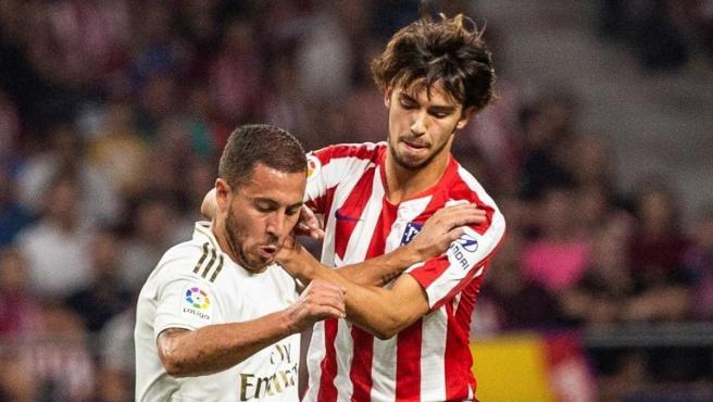 Hazard protege un balón ante la oposición de Joao Félix.