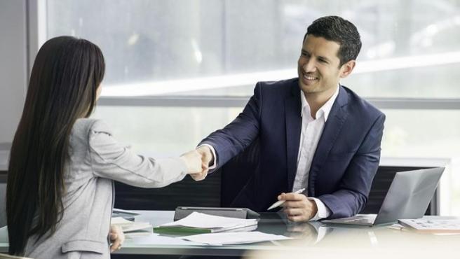 Un hombre y una mujer cierran un trato con un apretón de manos.
