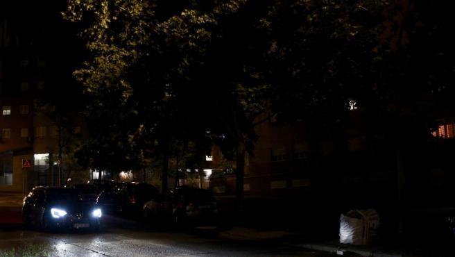 Una zona de la calle La Diligencia, en Puente de Vallecas, a oscuras pese a ser iluminada por los focos de un coche.