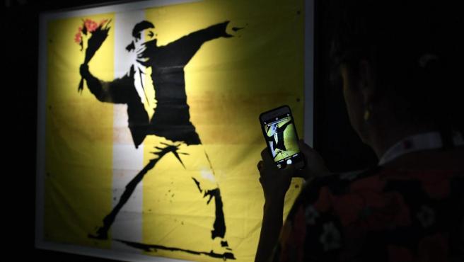 Un hombre fotografía una obra de Banksy, que se exhibe en la exposición 'El arte de Banksy', que abre sus puertas al público en el Entertainment Quarter de Sídney (Australia).
