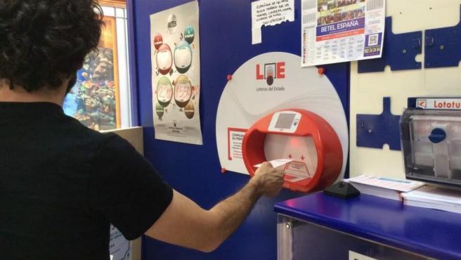 Una persona comprueba un boleto de Euromillones en una administración de Lotería.