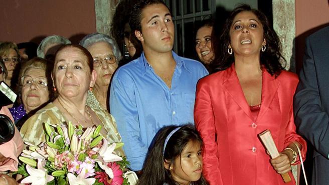 Ana María Martín, con un ramo de flores en la mano, junto a Isabel Pantoja (de rojo), Kiko Rivera (detrás) e Isa Pantoja, en primer plano, en una imagen de 2002.