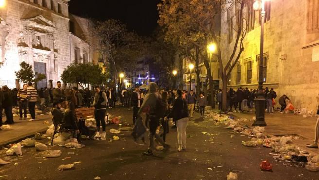 Aspecto que presentaba la céntrica plaza del Mercado de València tras una verbena de las Fallas de 2019, con grandes cantidades de basura acumulada junto a la Lonja y la iglesia de los Santos Juanes.