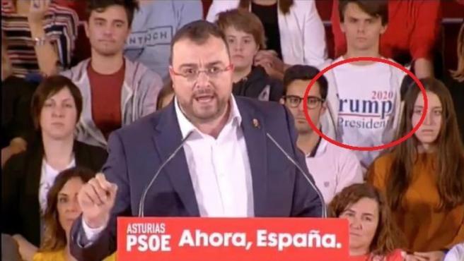Un joven 'trolea' un mitin del PSOE llevando una camiseta de apoyo a Trump.