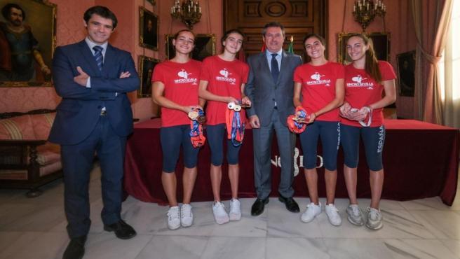 Imagen del encuentro del alcalde de Sevilla, Juan Espadas, y el delegado de Transición Ecológica David Guevara, con las nadadoras del equipo CD Sincro Sevilla.