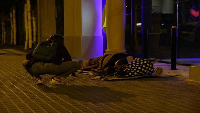 Un voluntari parla amb una persona sensellar al carrer de Barcelona.