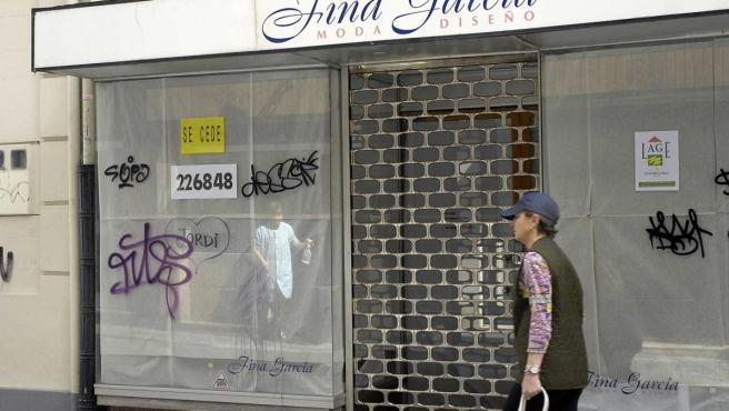 Una mujer pasea ante una tienda cerrada.