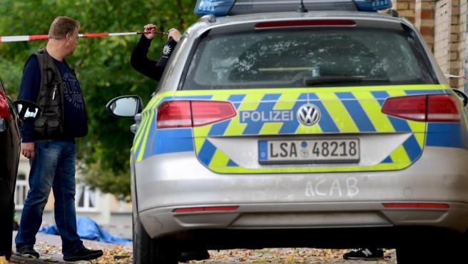 Policías frente a los cuerpos cubiertos de las víctimas del tiroteo en Halle, Alemania.