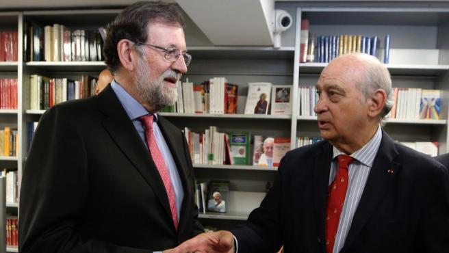 El expresidente, Mariano Rajoy (izq.), conversa con Jorge Fernández Díaz