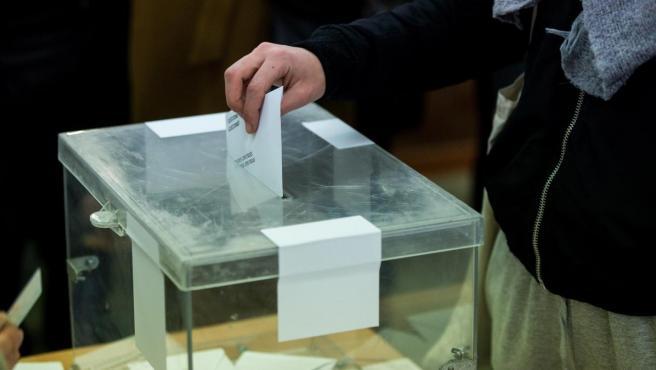 Un votante deposita un voto en una urna.