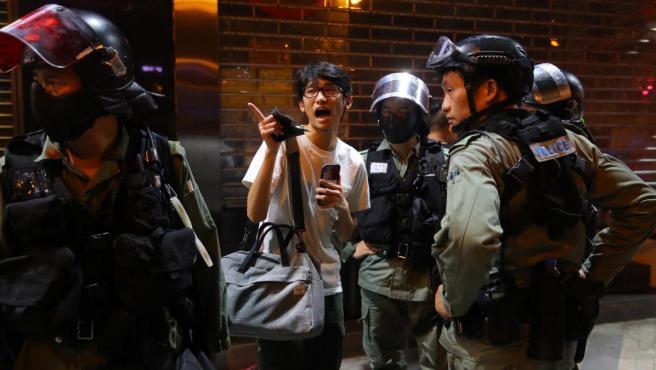 Policías hablando con un manifestante en Hong Kong.
