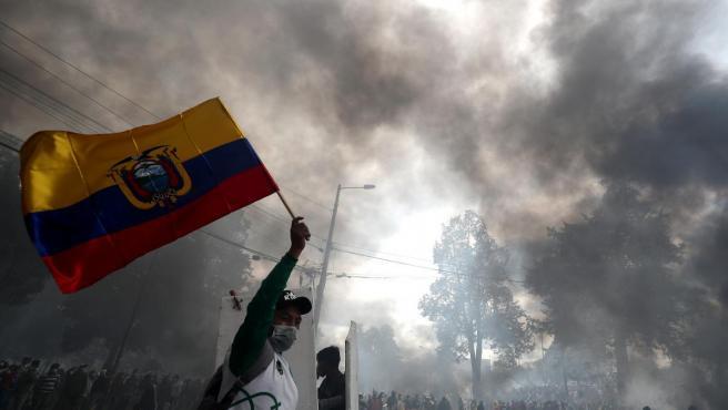 Un hombre ondea la bandera ecuatoriana mientras manifestantes se aproximan a la sede de la Contraloría General del Estado en Quito, Ecuador.