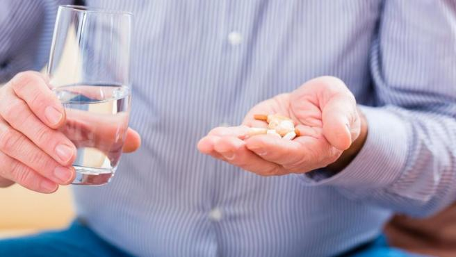 Imagen representativa de un hombre tomando medicamentos para su hemorragia digestiva.