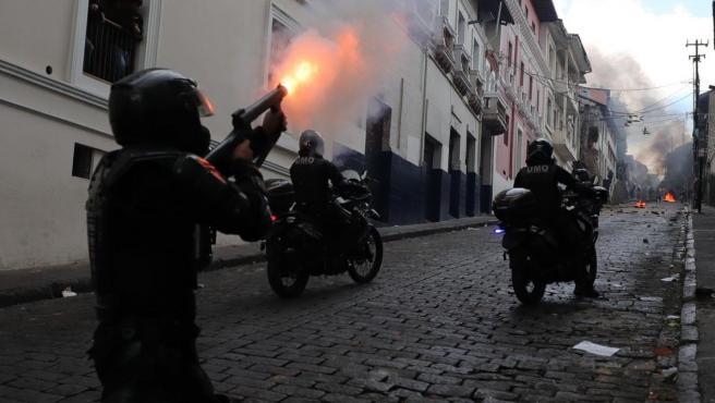 Miembros de la Policía se enfrentan con manifestantes, en el centro de Quito (Ecuador).