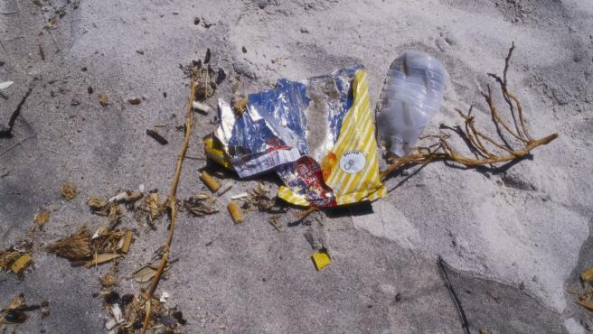 Playa contaminada por colillas de cigarrillos y residuos de plástico.