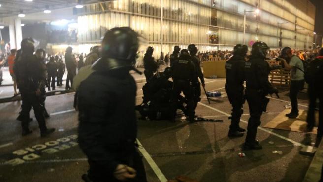 Mossos, ayer, frente a manifestantes en el aeropuerto de Barcelona.