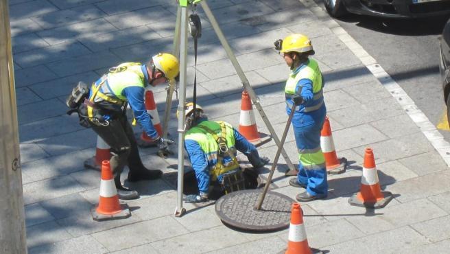 Seguridad en el trabajo, seguridad laboral, obreros con casco y chaleco reflectante, obra señalizada con conos, alcantarillado