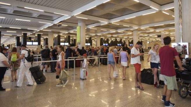 Turistas en la cola de facturación del aeropuerto de Palma de Mallorca.
