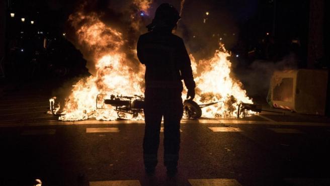 Un bombero observa como arde una moto en una de las hogueras prendidas por radicales, en una calle del centro de Barcelona, durante la segunda jornada de protestas tras la sentencia del procés.