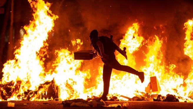 Un participante en las revueltas de Barcelona alimenta el fuego con cartones.