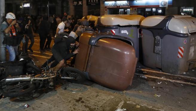Varios manifestantes vuelcan contenedores durante los disturbios en Barcelona.