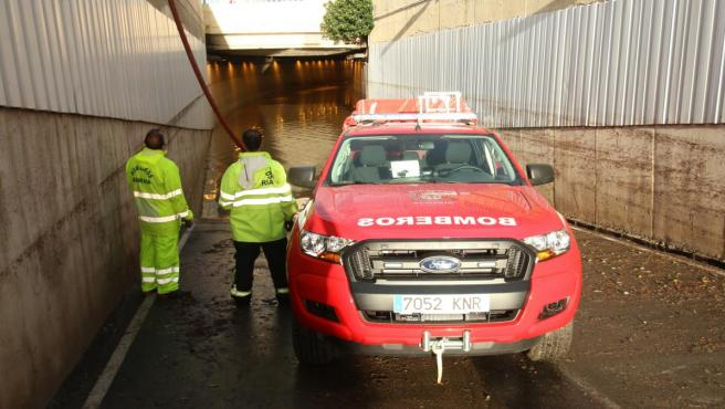 Bomberos a la entrada del tunel anegado por el temporal donde ha muerto una persona.