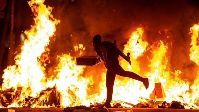Un manifestante echa al fuego un cartón durante la segunda jornada de protestas en Cataluña contra la sentencia del juicio del procés.