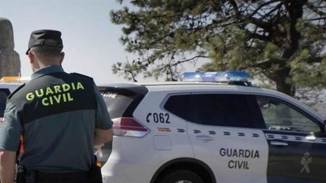 Agente de la Guardia Civil junto a un coche patrulla.